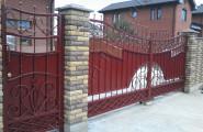 Кованые ворота с калиткой на каменных столбах после установки
