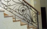 Кованые перила с деревянными поручнями на лестнице