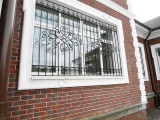 Решетка кованая окна в кирпичном доме