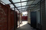Металлический навес между стеной дома и забором в частном доме