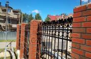 Секции кованого забора с кирпичными столбами