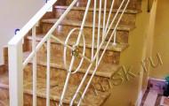 Нижний этаж лестницы с коваными перилами