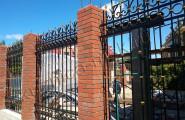 Кованый забор на кирпичных столбах